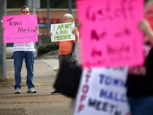 Andy O'Neill (left) and Martha Johnson join a small group of protesters on the corner of Highland Street and Poplar Avenue as Rep. David Kustoff talks with the Memphis Bar Association at a nearby Jason's Deli.