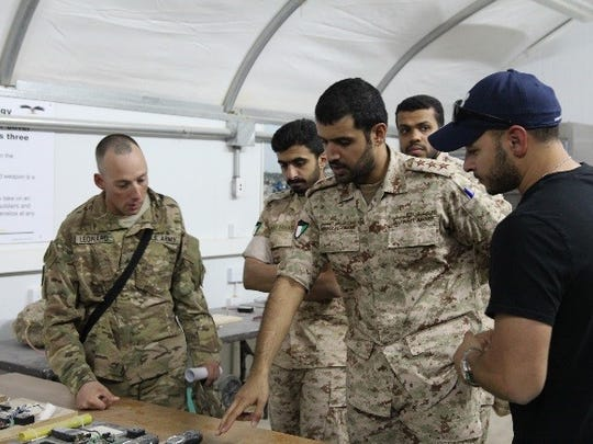 Sgt. Thomas Lenard, Bravo Company, 2nd Engineer Battalion, reviews different types of improvised explosive devices with Kuwaiti Land Force engineer officers.