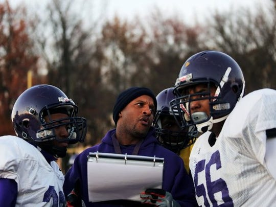 Trezevant High School head football coach Teli White shows his athletes a page from the team's playbook during football practice on Dec. 3, 2015.