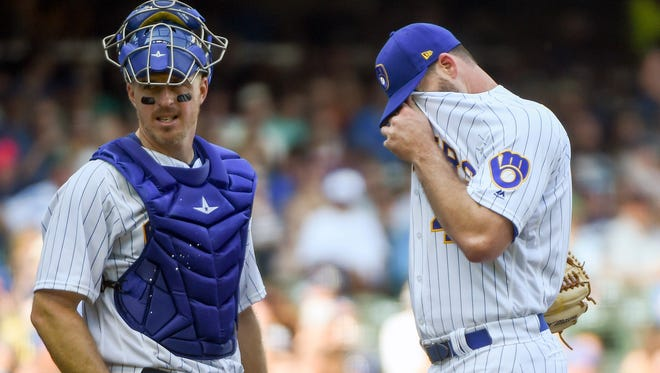 Brewers reliever Boone Logan and catcher Erik Kratz wait for a pitching change in the sixth inning Saturday at Miller Park.