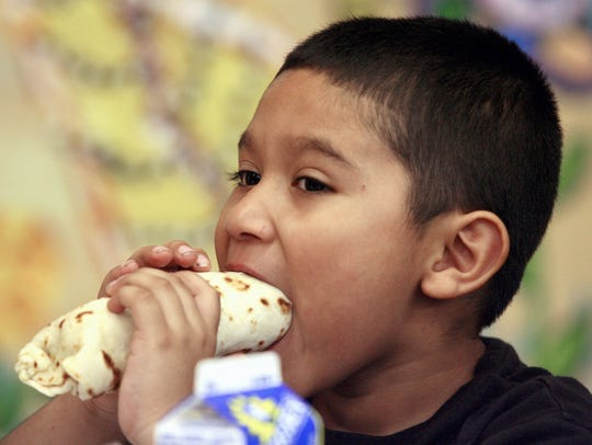 Juan Davila, age 6, eats a taquito of eggs and bacon.