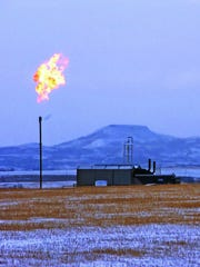 In this Feb. 25, 2015, file photo, a gas flare is seen at a natural gas processing facility near Williston, N.D.
