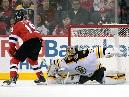Boston Bruins goaltender Anton Khudobin, right, makes a save on a penalty shot by New Jersey Devils center Travis Zajac (19) during the first period of an NHL hockey game Sunday, Feb. 11, 2018, in Newark, N.J. (AP Photo/Bill Kostroun)