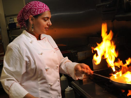 Maneet Chauhan, executive chef of Chauhan Ale & Masala House in Nashville, flames up a dish.