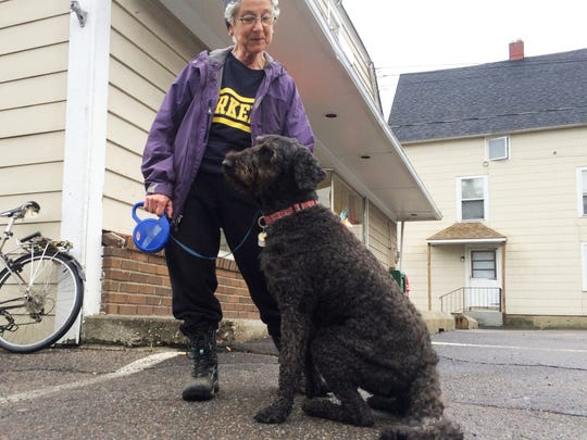 Louise Stoll pauses with her dog, Sheba, in front of Pine Street Deli in Burlington on Friday morning. Stoll is a supporter of the proposed redevelopment of the deli site to include residential apartments.