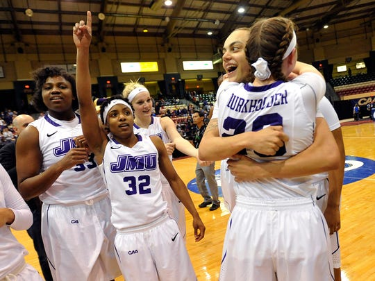 James Madison's Angela Mickens (32), celebrates with teammates, from left, Lauren Okafor, Jazmon Gwathmey and Kirby Burkholder after the Dukes beat Delaware in the CAA tournament final last season.