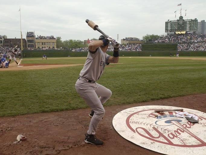 In this June 6, 2003, file photo, New York Yankees' Derek Jeter warms up in the on-deck circle in a baseball game against the Chicago Cubs at Wrigley Field in Chicago. Wrigley Field was  first time and time again in changing the way we watch baseball and the experience for fans in ballparks around the country. The historic ballpark will celebrate it's 100th anniversary on April 23, 2014.