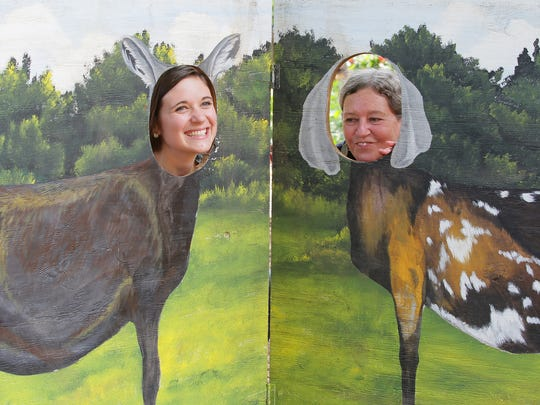 Katherine Locascio, left, and her mother Beverly Rainey, right, both of Seneca, place their face in a photo booth with painted goats during the Spring Means Babies at Split Creek Farm near Pendleton in Anderson County.