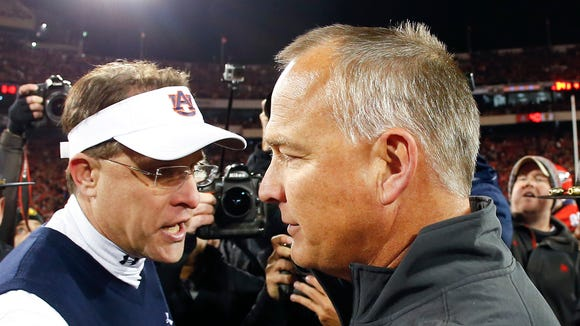 Georgia coach Mark Richt and Auburn coach Gus Malzahn meet at midfield after an NCAA college football game Saturday, Nov. 15, 2014, in Athens, Ga. Georgia won 34-7.