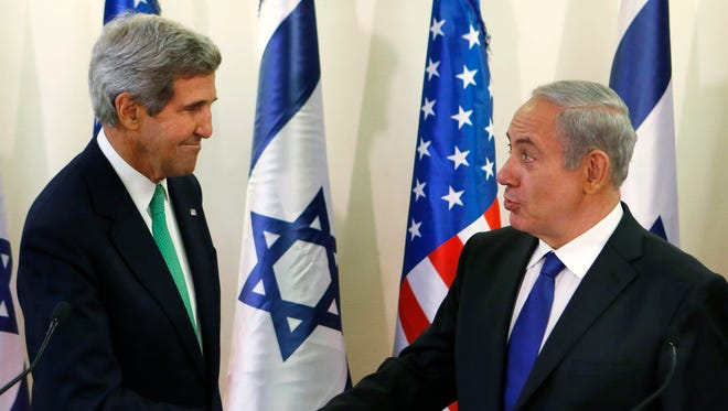 U.S. Secretary of State John Kerry, left, shakes hands with Israel's Prime Minister Benjamin Netanyahu after speaking to the media at the prime minister's office in Jerusalem, Israel on Sunday.