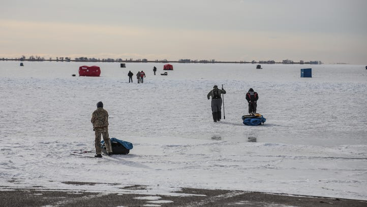 People make their way out onto the ice to fish on the
