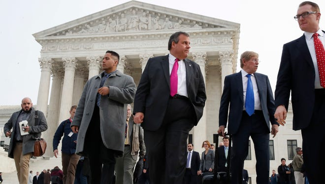 New Jersey Gov. Chris Christie, center, leaves the Supreme Court where a case on sports betting is being heard, Monday, Dec. 4, 2017