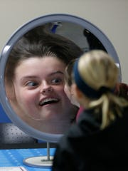 Sara Graff plays with her reflection in a concave mirror during the Michigan Tech Mind Trekkers event that drew 2,000 middle school students to NWTC to participate in displays of science, technology, engineering and math.