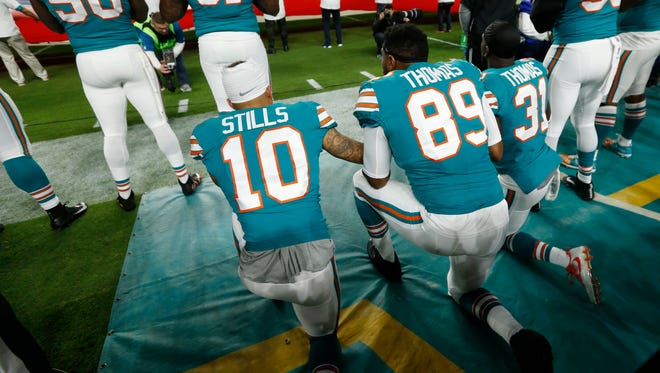 Miami Dolphins wide receiver Kenny Stills (10), tight end Julius Thomas (89) and strong safety Michael Thomas (31), kneel during the National Anthem, before the first half of an NFL football game against the New England Patriots, Monday, Dec. 11, 2017, in Miami Gardens, Fla. (AP Photo/Wilfredo Lee)