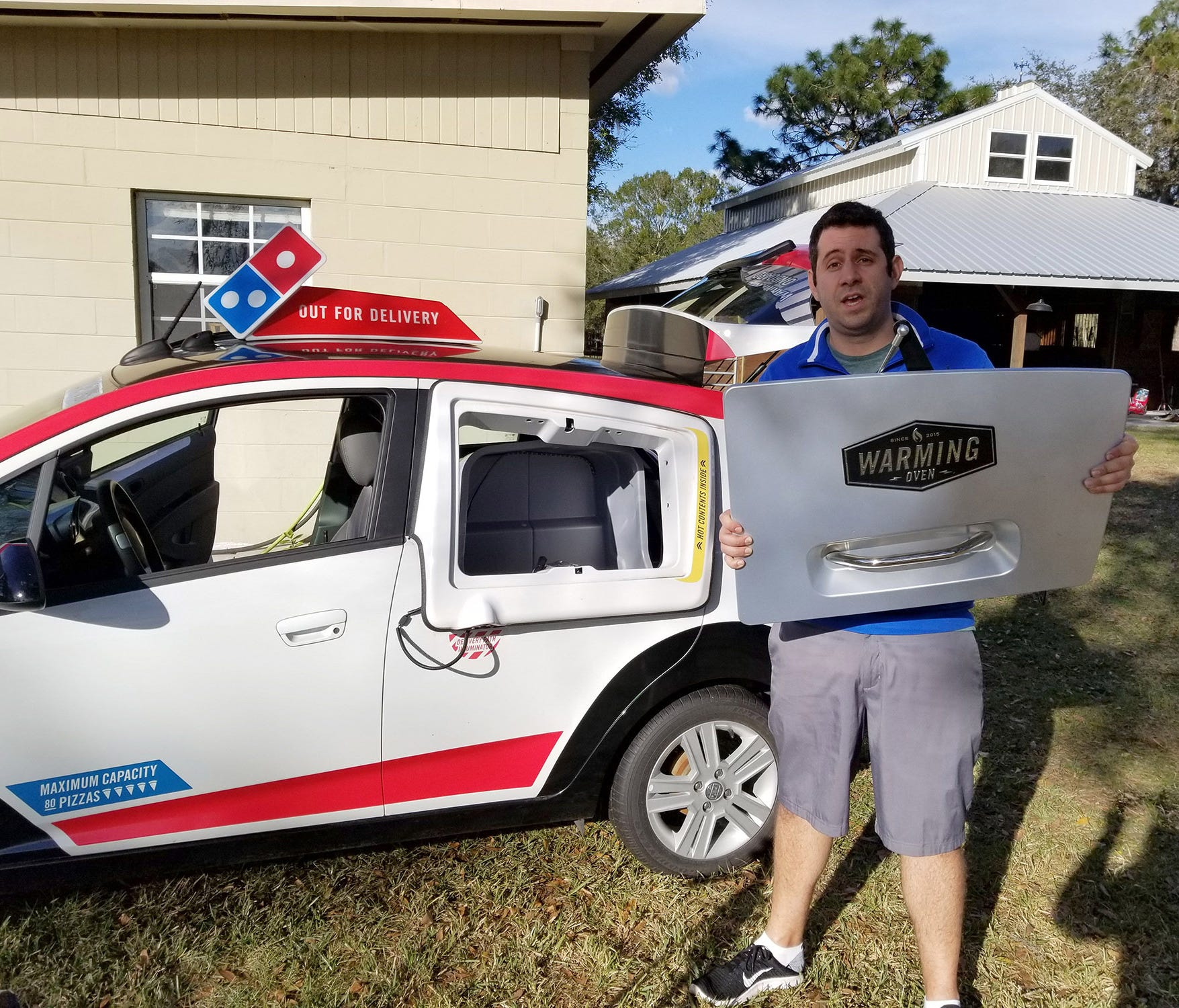 YouTube personality known as Samcrac is facing a potential legal threat from Domino's Pizza. He is with the Domino's Pizza delivery car he bought at auction and repaired.