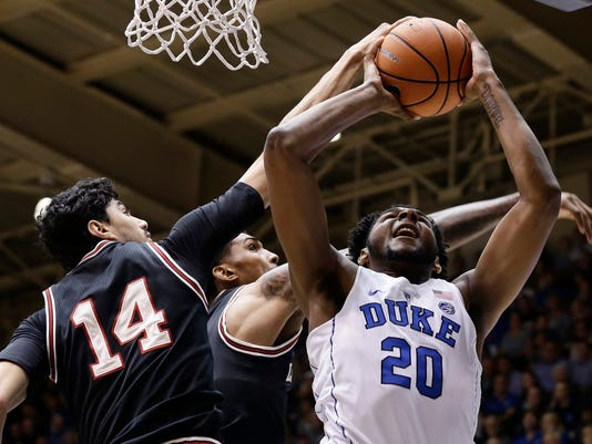 Duke's Marques Bolden (20) tries to shoot against Louisville's Anas Mahmoud (14) and Malik Williams during the first half of an NCAA college basketball game in Durham, N.C., Wednesday, Feb. 21, 2018. (AP Photo/Gerry Broome)
