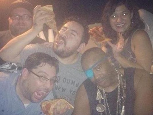 Dave Acosta, bottom left, and friends Bobby Smith, top right, Albert Perez, center, and Nicole Martinez enjoy a slice with rapper Slick Rick, bottom right, in Austin.