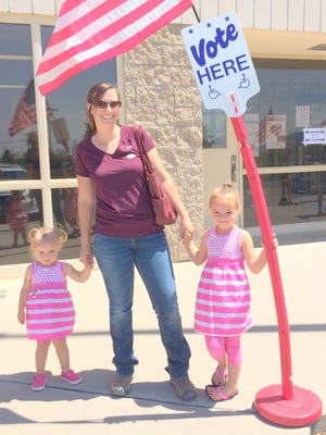 Kim Crumbley of Fort Bayard showed her daughters Dezia, right, and Alice about the voting process in New Mexico. She visited the New Mexico Army National Guard on Tuesday afternoon.