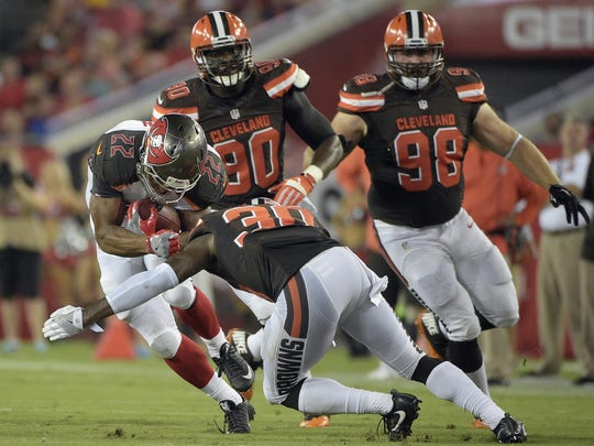 Tampa Bay Buccaneers running back Doug Martin (22) is hit by Cleveland Browns' Derrick Kindred (30) during the first quarter of an NFL football game Friday, Aug. 26, 2016, in Tampa, Fla. (AP Photo/Phelan M. Ebenhack)