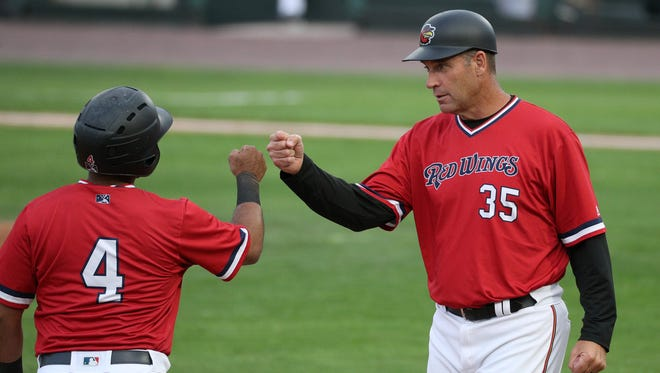 Rochester manager Joel Skinner congratulates Gregorio Petit at third base during a game last season. Skinner will return to manage the Red Wings in 2019.