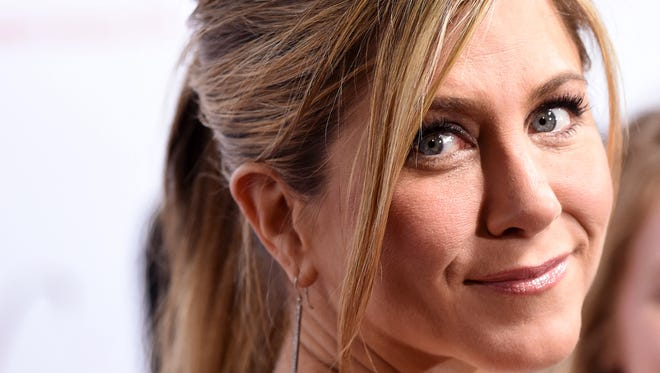 """Jennifer Aniston, a cast member in """"Cake,"""" turns back for photographers at the premiere of the film at Arclight Cinemas on Wednesday, Jan. 14, 2015, in Los Angeles. (Photo by Chris Pizzello/Invision/AP )"""