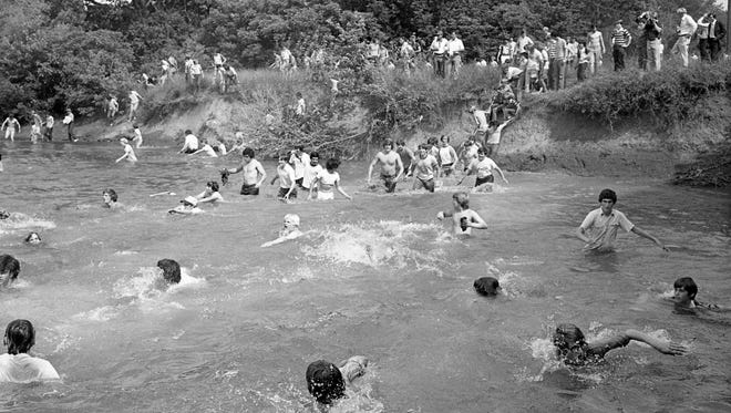 Members of the Platos are scrambling for dry land after falling in Battle Ground Academy annual tug of war on the West Harpeth River near Franklin May 10, 1976.