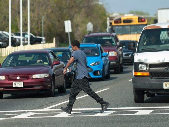A pedestrian crosses Route 130 South, at the intersection
