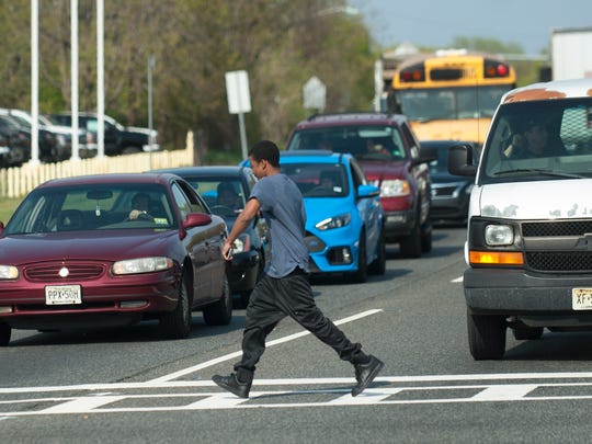 A pedestrian crosses Route 130 South, at the intersection of Route 130 and East Federal Street, in Burlington City. Route 130 is one of the state's most deadliest highways for pedestrians.