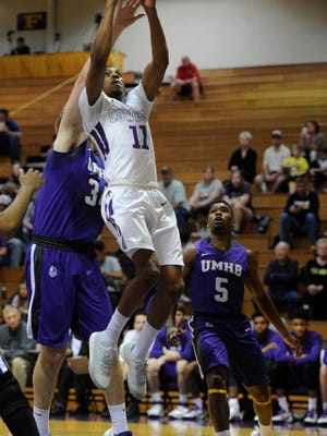 Hardin-Simmons' Christian O'Neal (11) lays in a shot past Mary Hardin-Baylor's Austen Stolte (34) during the first half of the Cowboys' 77-76 win on Saturday, Feb. 18, 2017, at HSU's Mabee Complex.