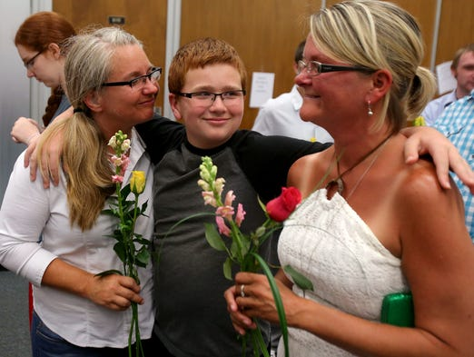 Aiden Murphy, 11, smiles as his mothers Kimberly Trojan, left, and Jackie Cornell wait in a large crowd for their marriage license inside the City County Building, Wednesday, June 25, 2014. A federal judge ruled Wednesday that Indiana's ban on gay marriage is unconstitutional.