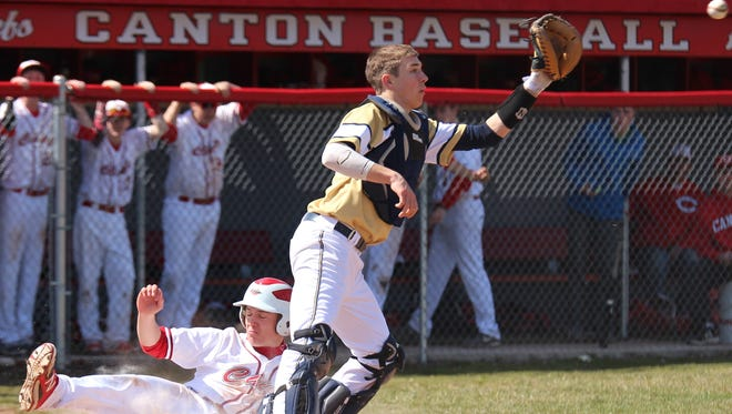 Beating a high throw to the Detroit Country Day catcher to put Canton up 7-6 during the sixth inning of Saturday's Game 1 is Canton senior Andrew Loehnis.