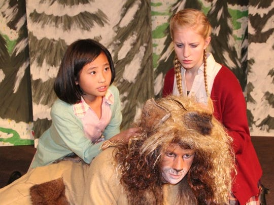 "Hannah Li as Lucy, left, and Catherine Vessey as Susan try to comfort Aslan played by Jacob Hueller in S.K.I.T. Theatre's production of ""The Lion, the Witch and the Wardrobe."" The group will hold theater camps this summer."