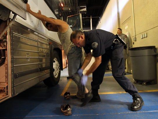Agente de ICE revisa a un detenido.