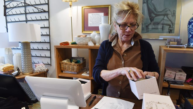 Haldora Bjornsson, owner of Haldora in Rhinebeck, goes over the inventory numbers for some hair brushes at the front desk.