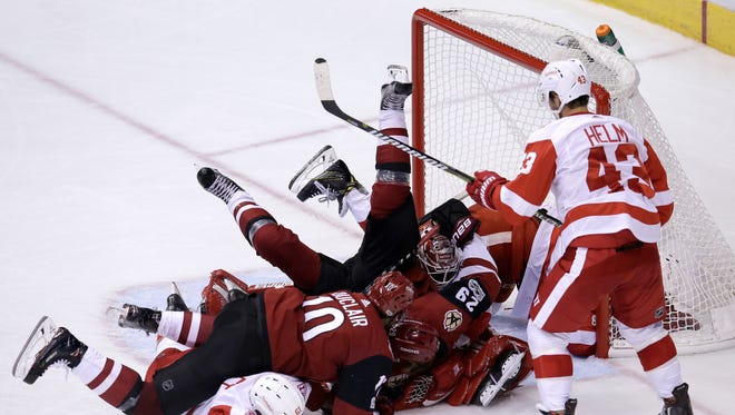 Arizona Coyotes' Anthony Duclair (10) and Mario Kempe (29) charge the net over Detroit Red Wings defenseman Xavier Ouellet (61) and goalie Jimmy Howard (35), as Darren Helm (43) watches during the third period of an NHL hockey game, Thursday, Oct. 12, 2017, in Glendale, Ariz. The Red Wings defeated the Coyotes 4-2. (AP Photo/Rick Scuteri)