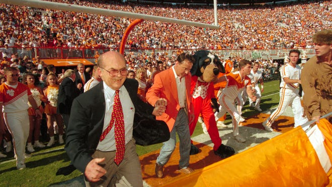 "University of Tennessee president Joe Johnson and Chattanooga businessman John Thornton run through the ""T"" on Sept. 30, 1995, before UT's homecoming game against Oklahoma State. Thornton donated $1 million to the university and asked if he could run through the ""T"" in return."