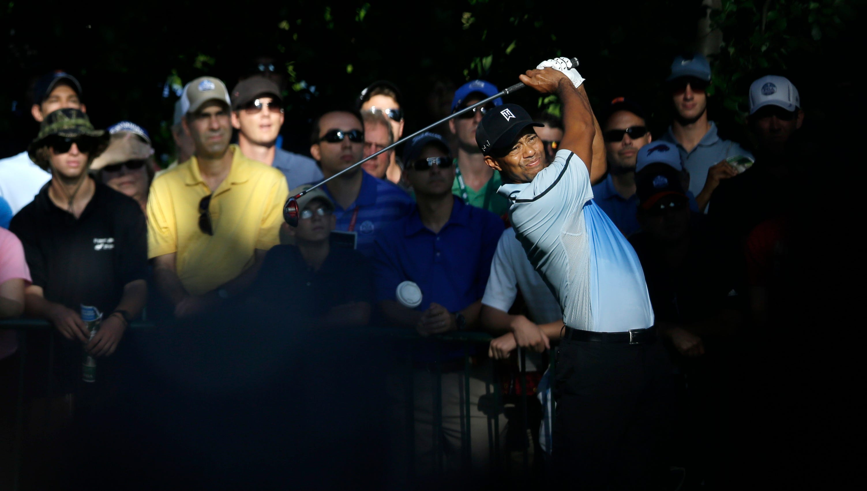 Tiger Woods watches his tee shot on the first hole.