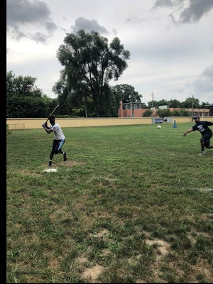 Indy Thunder players Darnell Booker (pitching) and Corey White (hitting) practice Beep Baseball for visually impaired players. The team is going for its third consecutive national title.