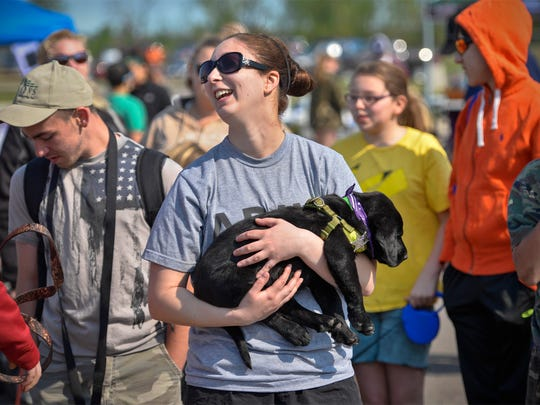 Destiny Vogel, St. Joseph, cuddles Titan, an 8-week-old black Labrador puppy, as she listens to instructions for Saturday's Bark for Life in Sartell.