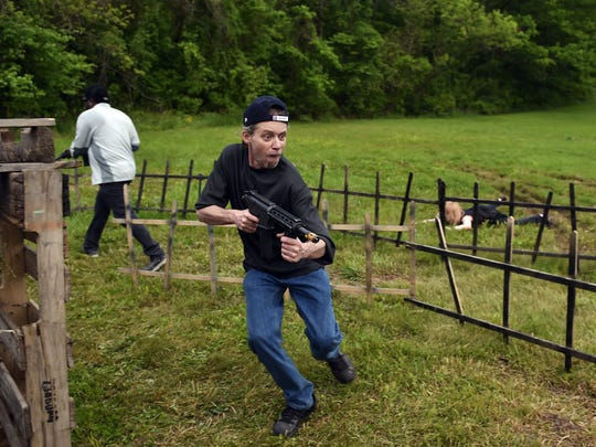 Rusty Kratzer of Harrisburg aims at a zombie, not pictured, while making his way through a Zombie Apocalypse Live event Friday, May 20, 2016, at Halloween Park in Newberry Township. Zombie Apocalypse LIVE, which is on tour and is making stops from Tennessee to California, provides a live-action zombie-shooting experience for teams of people who are armed with infrared military training replica weapons.