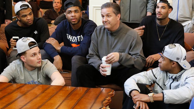 From left, Aaron Harrison, Brian Long, Andrew Harrison, John Calipari, Willie Cauley-Stein, Tyler Ulis and other members of Kentucky's men's basketball team watch the NCAA college basketball tournament selection show at the home of head coach John Calipari in Lexington, Ky. March 15, 2015