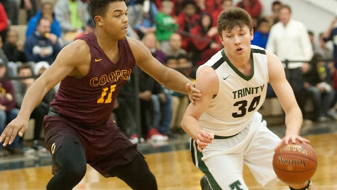 Cooper guard Brayden Runion tries to slow down Trinity guard Lucas Burkman at the top of the key.