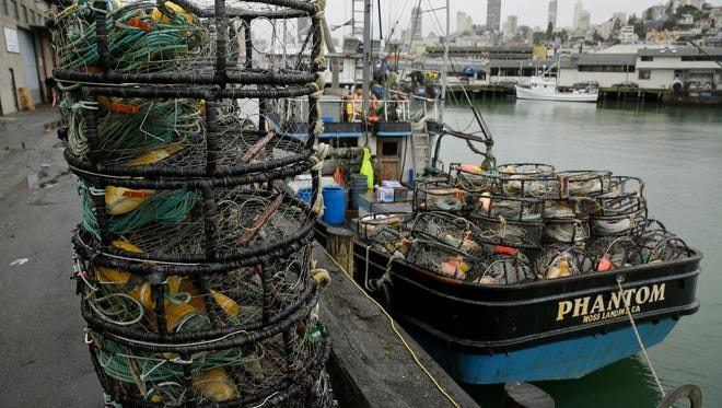 Crab pots sit on a processing pier and the back of a boat at Fisherman's Wharf Tuesday, Jan. 3, 2017, in San Francisco.