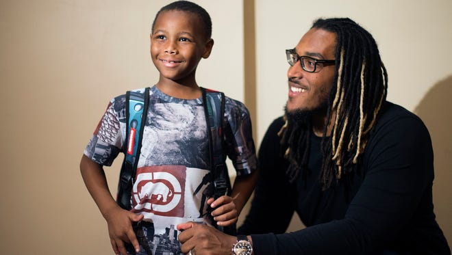 From left, Tyren Johnson, 6, of Detroit, smiles as he poses for a photo with offensive tackle for the Los Angeles Chargers and Detroit native, Joe Barksdale, during a backpack and school supplies handout .