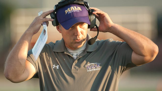 Male head football coach Chris Wolfe listens to his coaches on the headset.25 August 2017