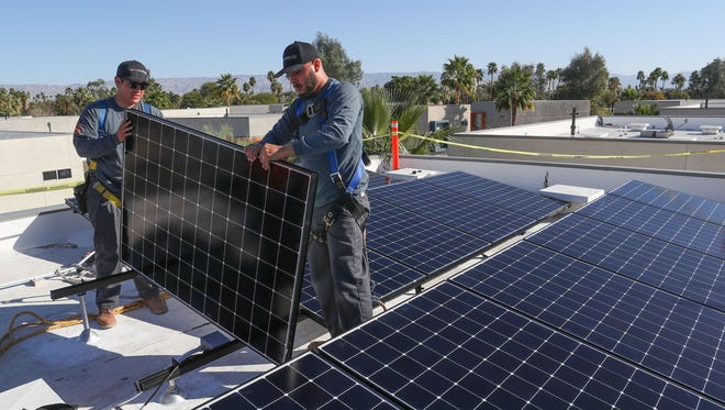 Renova solar technicians Jeff Flores, left, and Luis Banuelos install new solar panels on a Palm Springs home, February 6, 2018.