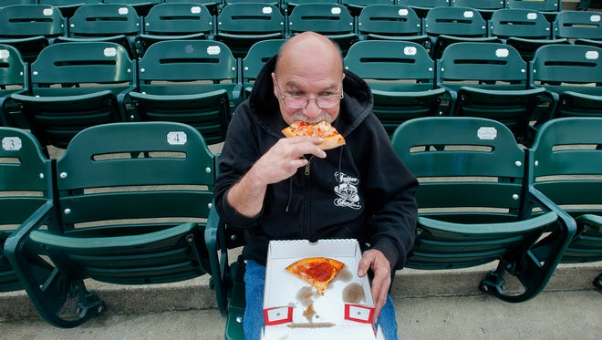 Ralph Dutther of Pleasure Ridge Park enjoys some hot pizza during the cool weather season opener of the Louisville Bats. 
