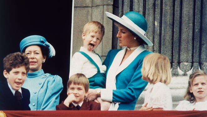 In this June 11, 1988 file photo Britain's Prince Harry sticks out his tongue for the cameras on the balcony of Buckingham Palace in London, England following the Trooping of the Colour. Princess Diana holds Harry, as a smiling Prince William sits in front, and Lady Gabriella Windsor is seen on the left.