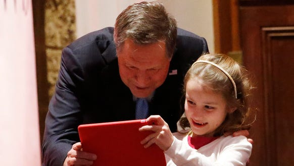 John Kasich looks at an iPad held by Ted Cruz's daughter