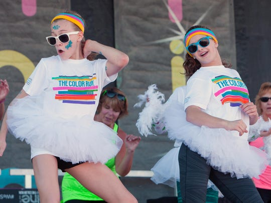 Eva Phair, left, 13 of Cornwall and Katherine Reeves, 14 of Essex show some Jazzercise moves on stage to help warm up the massive crowds before the Color Run.